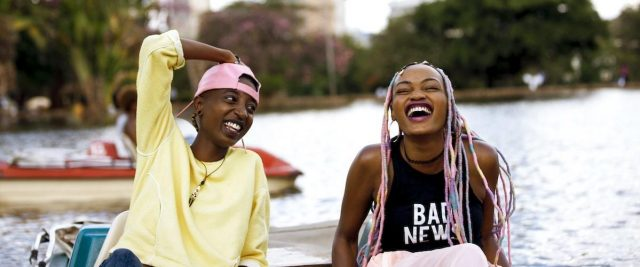 Two African women sitting in a boat and laughing.