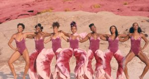 Image of Janelle Monae and 6 other black women wearing pink outfits