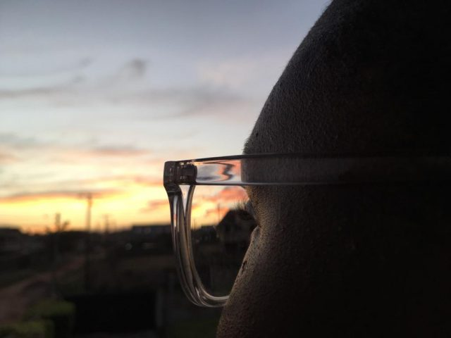 Image contains a woman in glasses watching the sunrise